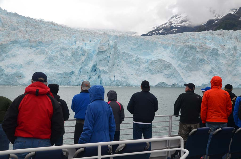 "Passengers on the Orca Voyager gather on deck to watch ""calving"" of the glaciers – the process in which large chunks of snow and ice break away from the glacier and fall into the Gulf of Alaska with a thunderous roar. Hours can pass between events, or a dozen can occur in rather rapid succession."