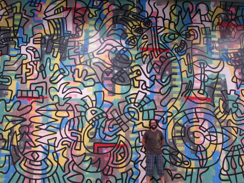 Santos Orellana stands in front of his largest mural yet. He started with the infinity symbol, or the figure eight, in the upper left corner and worked from there. Photo by Ellen Wright