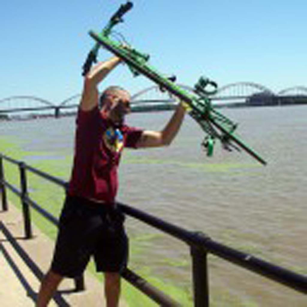 "Author Brian David Bruns ceremoniously mimics dipping his front bicycle wheel in the Mississippi River to signal the completion of the seven-day, 450-500-mile annual ride across Iowa known as RAGBRAI. He writes about the adventure in ""Rumble Yell."""