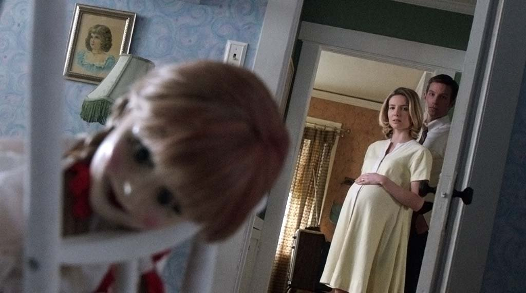 """Mia (Annabelle Wallis) and John (Ward Horton) with the Annabelle doll in the horror film """"Annabelle."""" Photo courtesy of Warner Bros. Pictures"""