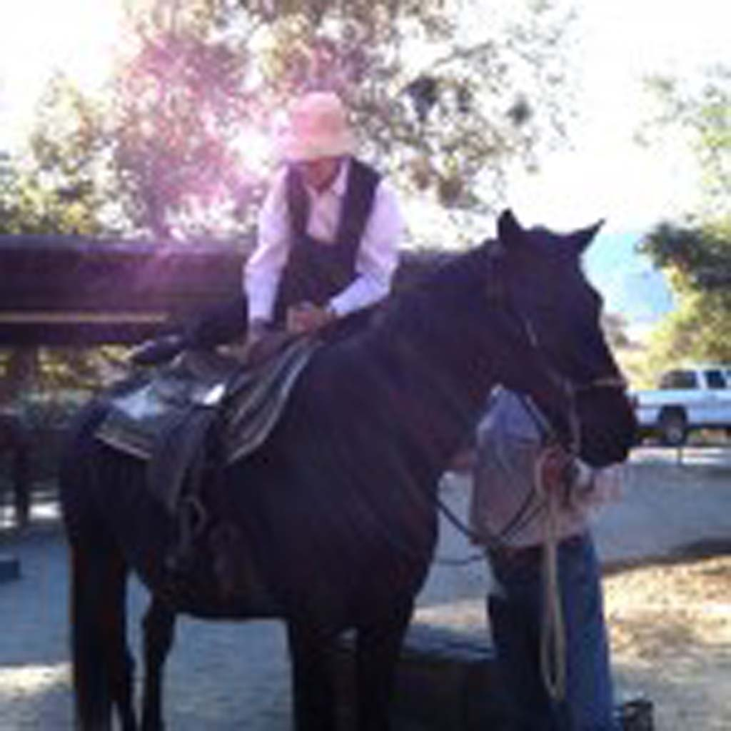 Cheryl Huse of La Jolla mounts one of Alisal's 70-some horses in preparation for a two-hour ride through some of the ranch's 10,000 acres. The property has belonged to the same family for more than 70 years, and is still a working ranch. Riders can see cattle grazing in the scenic backcountry. (Photo by E'Louise Ondash)