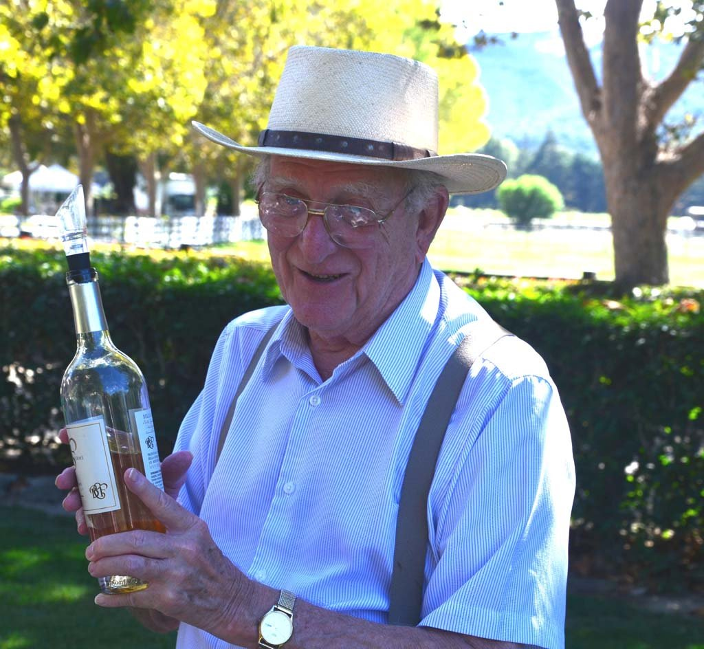 """BellaCavalli-Dr. Jack Lockwood – Dr. Jack Lockwood offers visitors at Bella Cavalli Farms & Vineyard a sample of its unique white cabernet. The vineyard makes only 1,600 cases a year, and tastings are by appointment only. Bella Cavalli in Italian translates as """"beautiful horses."""" The vineyard's owners also raise and board show horses. ALL PHOTOS BY Jerry Ondash"""