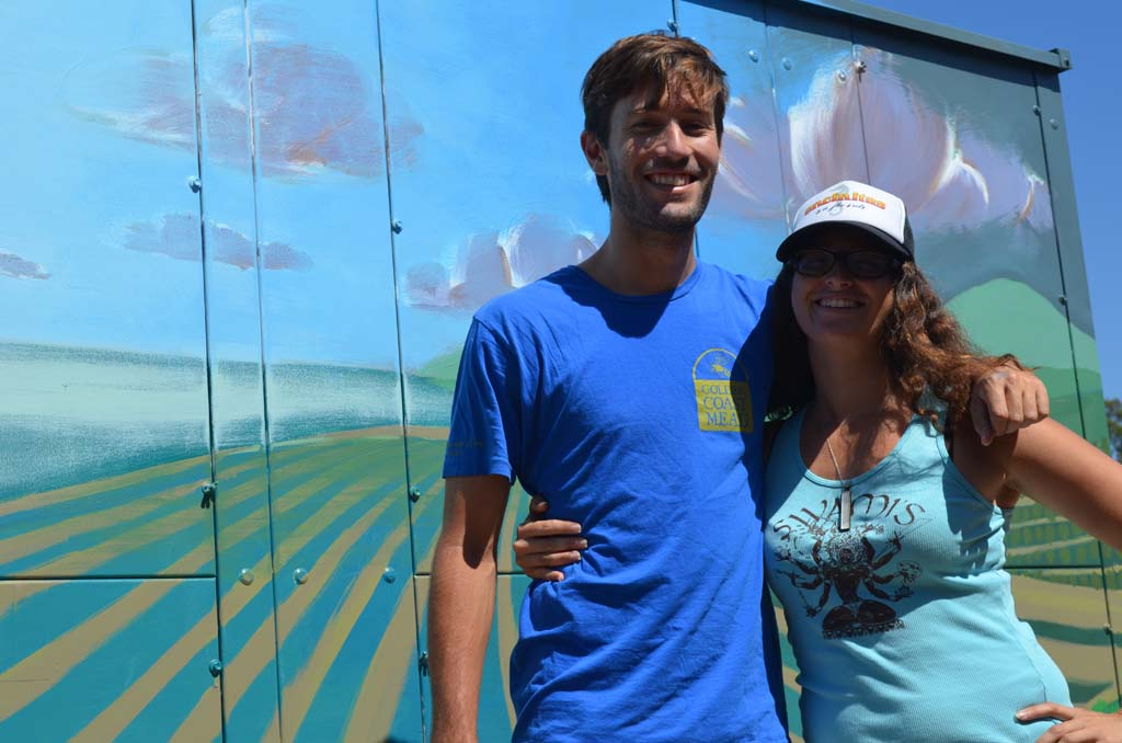 """Fallbrook artist Taylor Gallegos, left, and Paint Encinitas Founder Jacqueline """"Jax"""" Meyers in front of the newly completed mural at the Encinitas Union School District's agricultural and horticultural learning lab. Photo by Tony Cagala"""