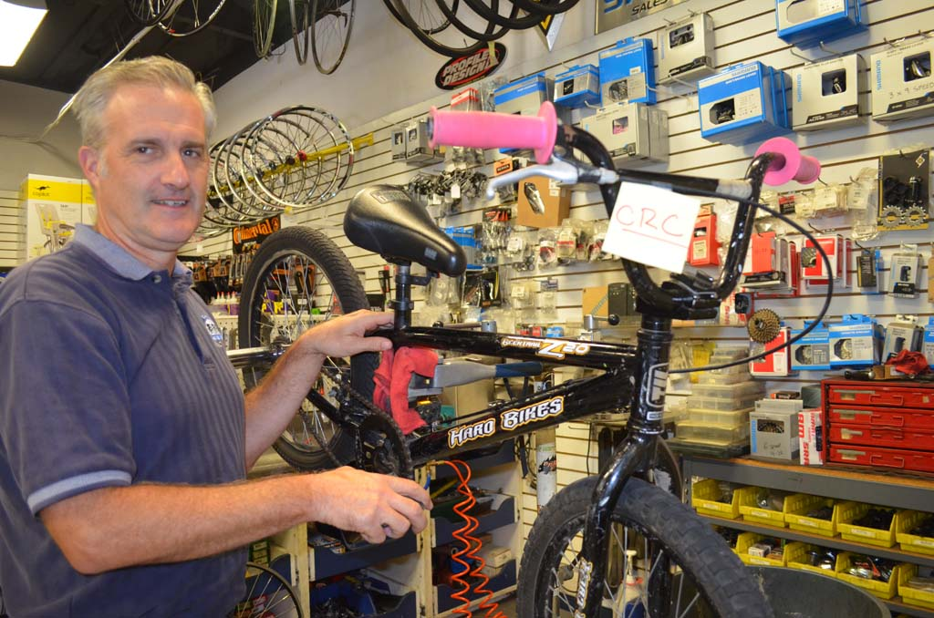 Co-owner of El Camino Bike Shop Will Schellenger is helping to refurbish old bikes that will be given to children of low-income families later this year. Photo by Tony Cagala