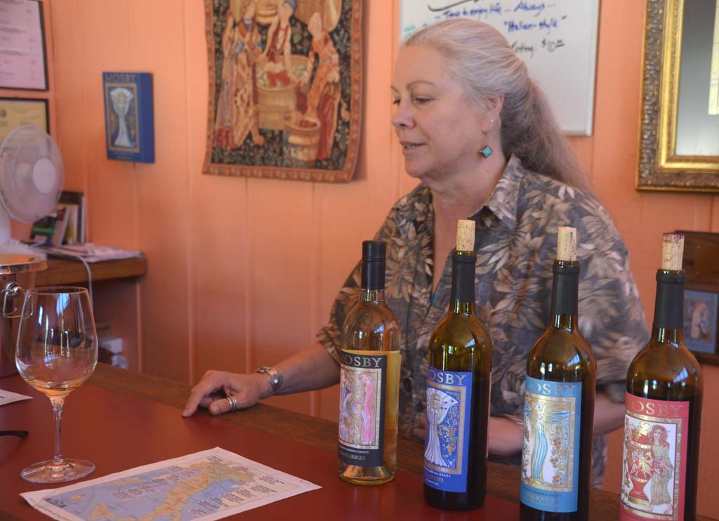 Ginny Burroughs pours Italian varietals at the Mosby Winery & Vineyard tasting room near Buellton. The ornate and intricate wine bottle labels were created by artist Robert Scherer of Appiano, Italy, and have won numerous awards.