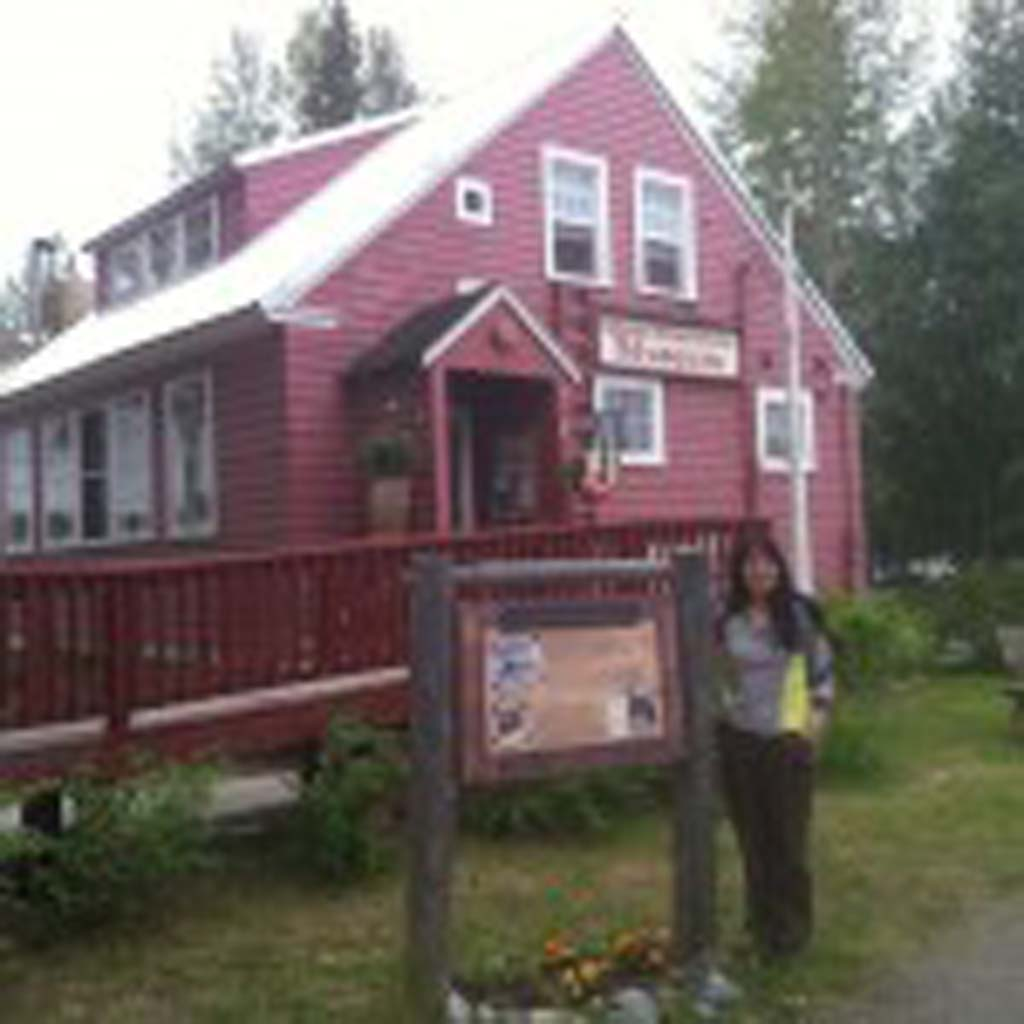 Panu Lucier of Anchorage visits her first home in Talkeetna, Alaska. Her father, Charles Lucier, was a teacher in this one-room schoolhouse in the mid-1950s, and her family lived in the apartment above. Today the schoolhouse is the Talkeetna Historical Society Museum and features artifacts from pre-statehood days.