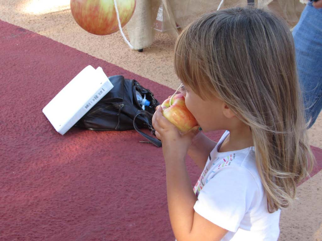 Mila Needleman, of Encinitas, bites into an apple at the bobbing for apple booth sponsored by Mayor Pro Tem Mark Packard's dental group. Children were also given cavity fighting lollipops.