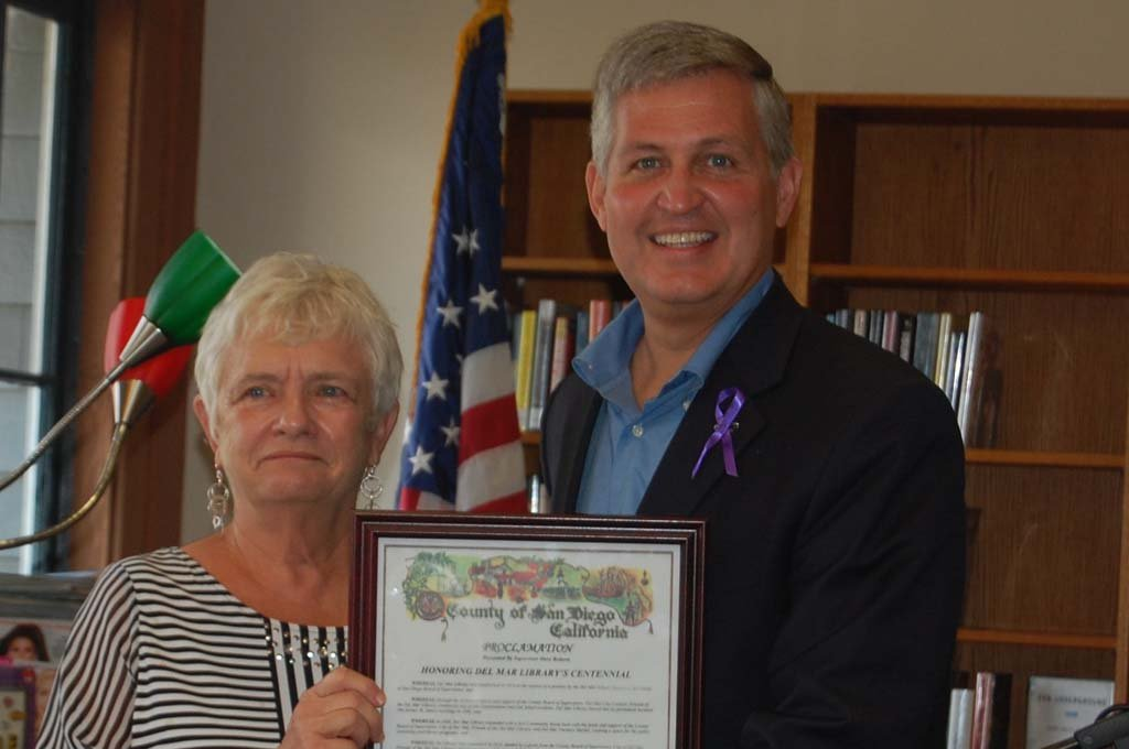 County Supervisor Dave Roberts presents Pat Freeman, president of Friends of the Del Mar Library, with a proclamation declaring Nov. 1, 2014, Del Mar Library Centennial Day in the county. Photo by Bianca Kaplanek