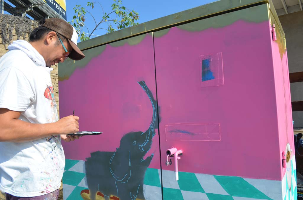 "Artist Seitaku ""Tak"" Aoyama works to finish his painting on a utility box on Coast Highway 101 near Encinitas Boulevard on Monday. Photo by Tony Cagala"