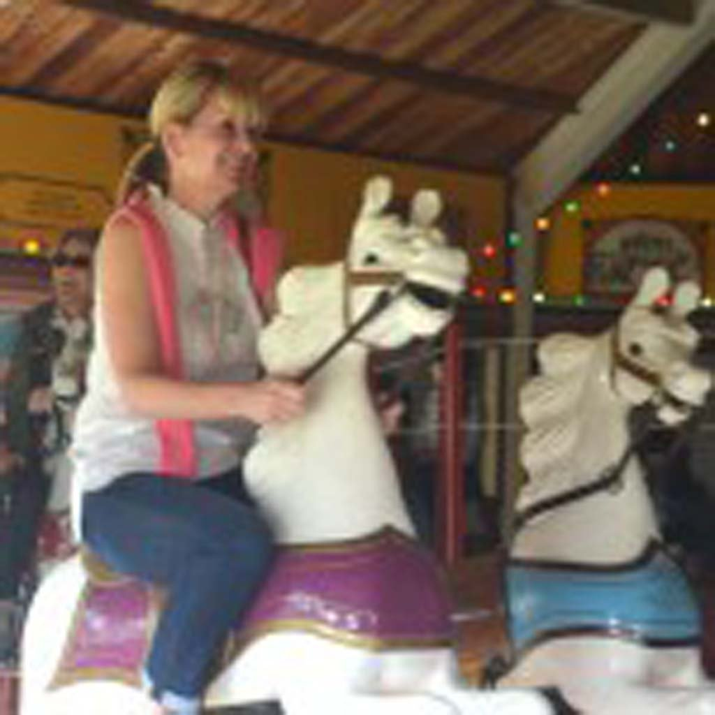 "Rebecca Sumpter-Rader of Kansas City catches a ride on one of the 24 hand-carved horses that grace the Parker Carousel, financed and patiently restored by the Dickenson County Historical Society. This one is more than a century old. The Parker Carousels (derived from ""carry-us-alls"") traveled nationwide with the C.W. Parker touring carnivals in the early 20th century. This carousel sits on the grounds of the Dickinson County Historical Museum in Abilene. Photo by Jerry Ondash"