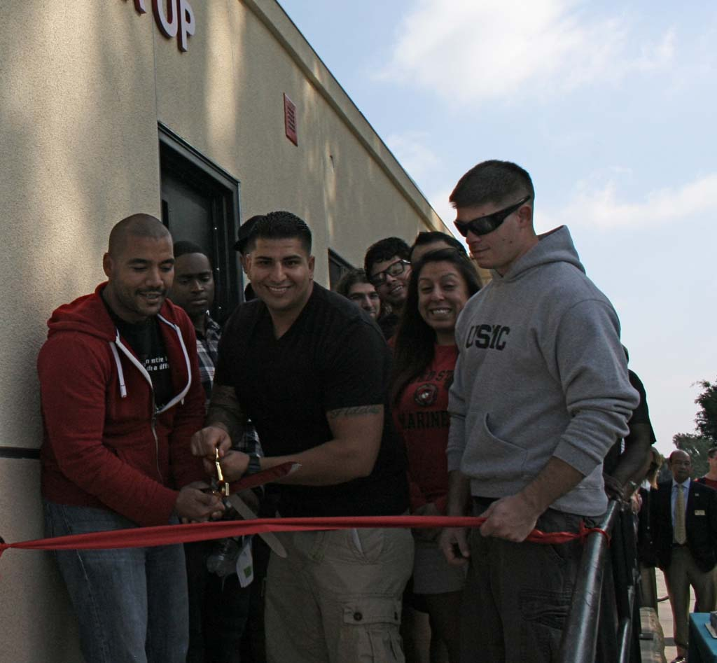 Military veterans and college students Gerald Borja, center, and Hector Rodriquez, left, cut the ribbon to open the Veterans Information Center Nov. 10. The center provides resources, counseling, a computer lab, and lounge. Photo by Promise Yee