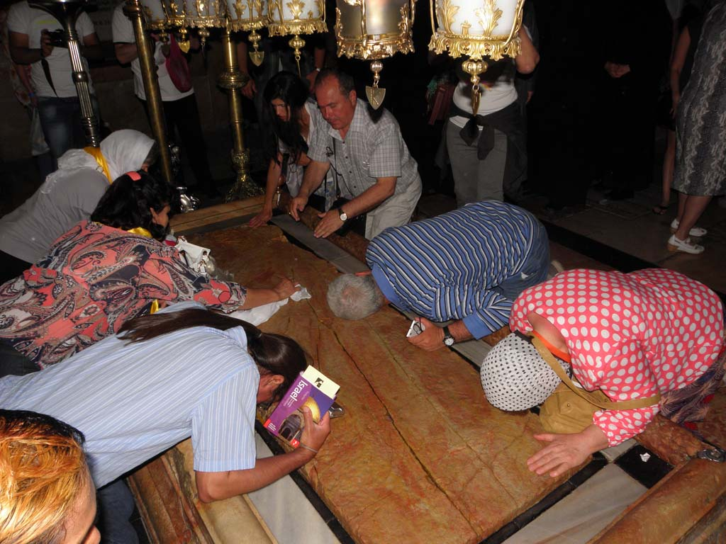This site, the Stone of Anointing (or Unction) is revered as the place where Jesus was laid out before burial. Visitors often throw themselves upon the stone and kiss it, which keeps the woman on the left busy disinfecting the stone.