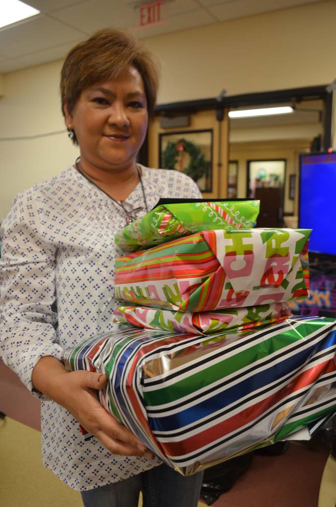 Mia Yamamota, program director of AmeriCare carries gifts to be delivered to seniors this holiday season. Photo by Tony Cagala