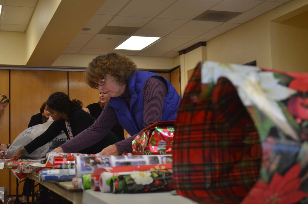 Sherrill Moore of San Marcos gets into the holiday spirit by helping to wrap gifts. Photo by Tony Cagala
