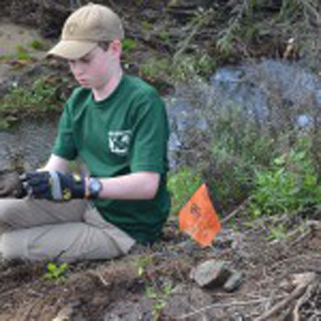 Breckin Uwins of Boy Scout Troop 777 adjusts his work gloves before making a dam around one of the new plantings. Photo by Tony Cagala