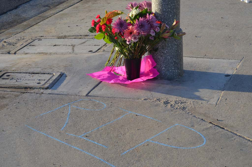 Flowers mark the scene where a female jogger was hit and killed when a vehicle swerved onto the sidewalk early Sunday morning. Photo by Tony Cagala