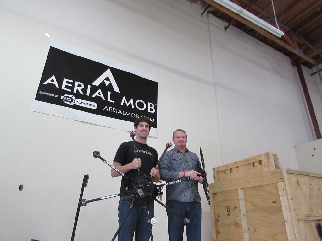 Co-founders Jonathan Montague, left, and Treggon Owens stand in their warehouse with one of their drones, which can cost upwards of $30,000. Photo by Ellen Wright