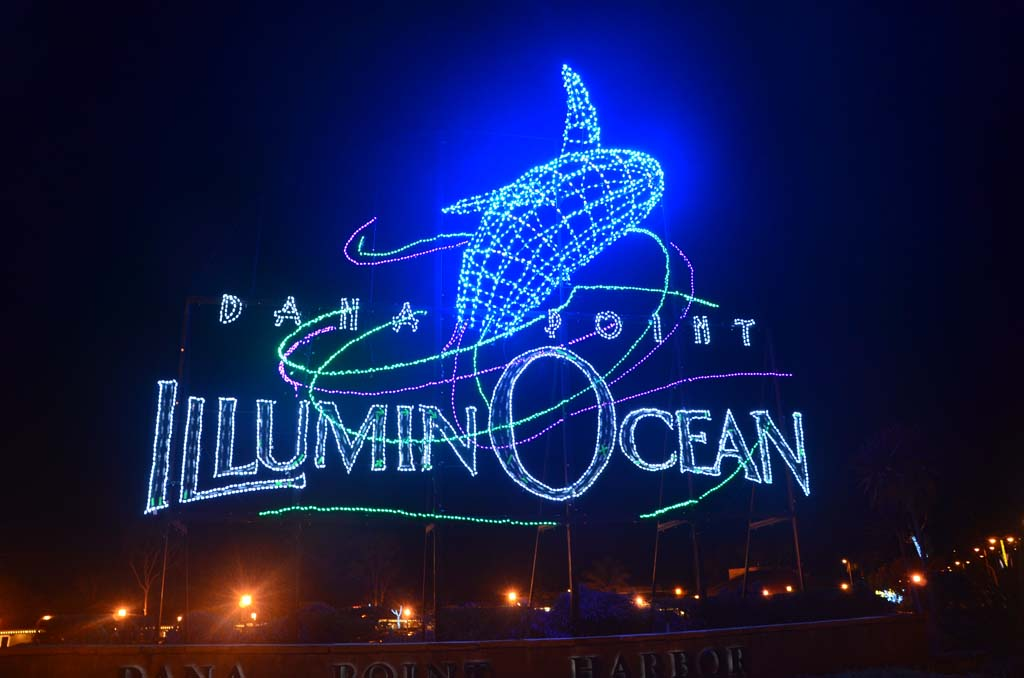 "This large sign at Dana Point Harbor Drive and Golden Lantern Drive welcomes visitors to the ""IlluminOcean – 40 Nights of Holiday Lights"" event in Dana Point Harbor. The free event runs through Jan 4. (Photo by Jerry Ondash)"