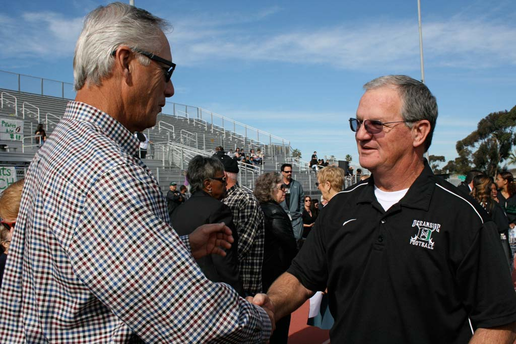 Former superintendent Larry Perondi shakes hands with Coach John Carroll before the dedication. Oceanside High School stadium was named after Carroll on Dec. 8. Photo by Promise Yee