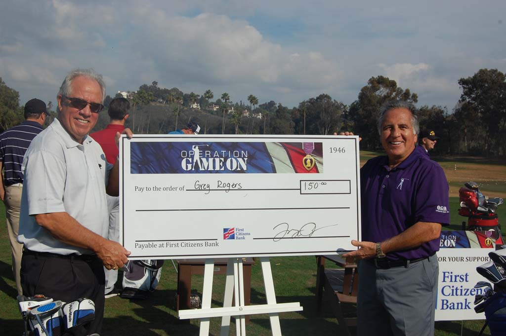 Encinitas resident Greg Rogers, left, poses with the oversized check indicating his winnings for sinking a hole-in-one from 50 yards out. Rogers was one of many participants who donated the funds back to Operation Game On, founded by Tony Perez, right. Photo by Bianca Kaplanek