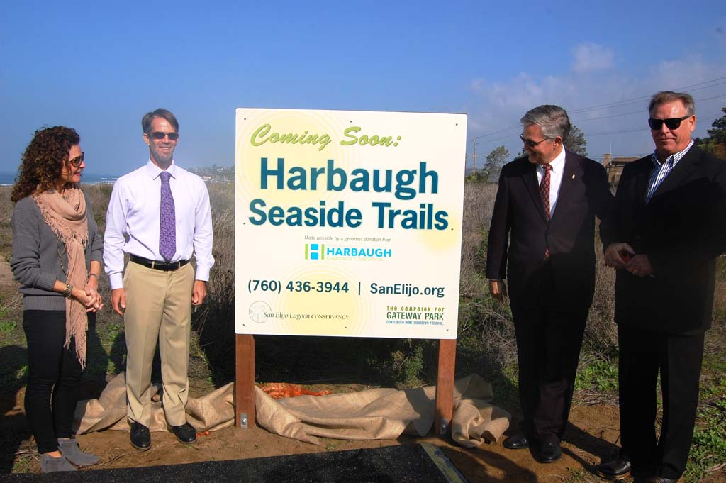 A sign announcing the new name for what has been called Gateway Park is unveiled during a Jan. 13 press conference by, from left, Solana Beach Mayor Lesa Heebner, San Elijo Lagoon Conservancy Executive Director Doug Gibson, County Supervisor Dave Roberts and Joe Balla, director of the George and Betty Harbaugh Charitable Foundation. Photo by Bianca Kaplanek