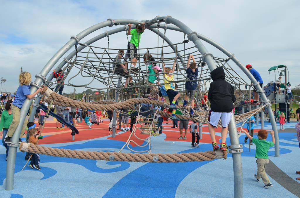 Youngsters play on a part of the new park's playground on Saturday. Photo by Tony Cagala