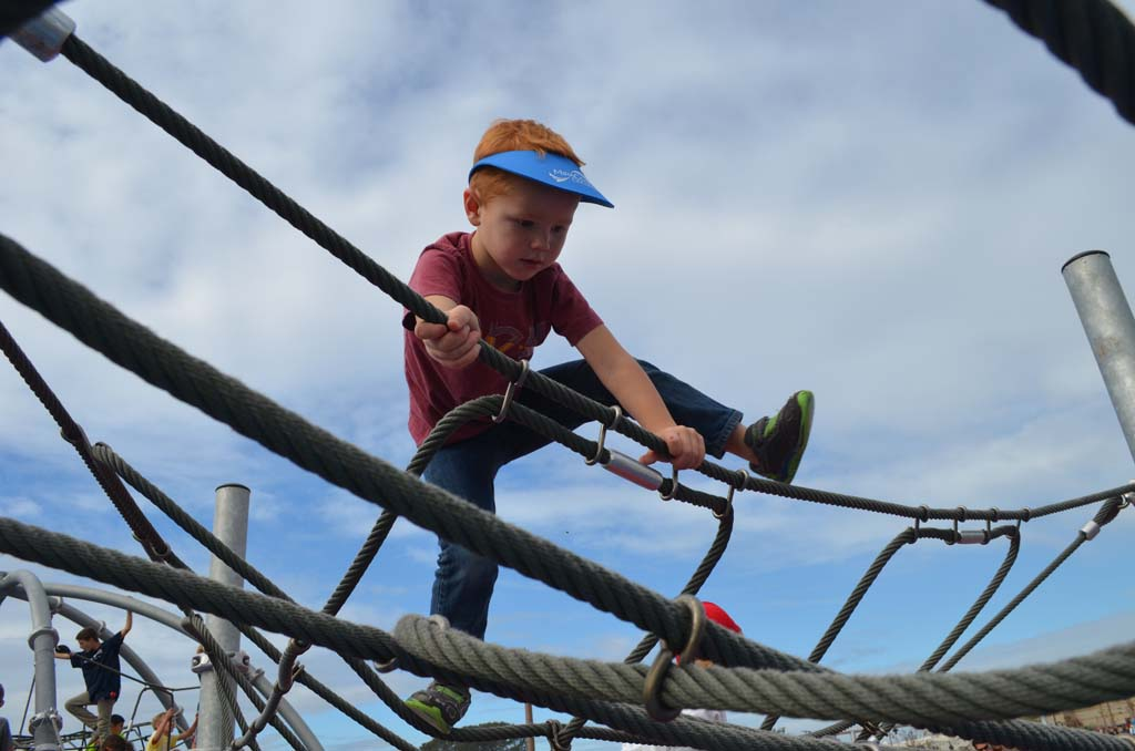 Nate Hougard climbs a rope ladder at the Encinitas Community Park. Photo by Tony Cagala
