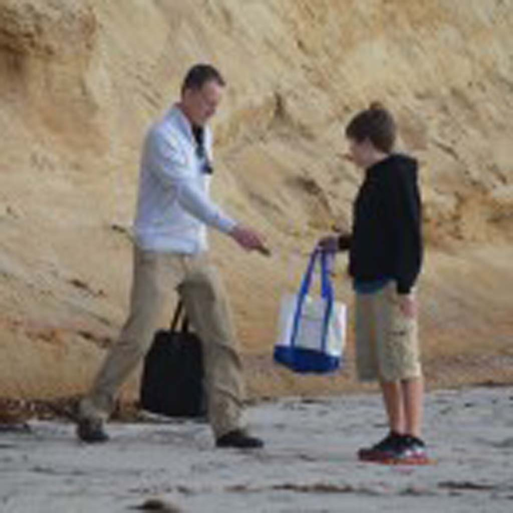 Rick Moore, left, of the Encinitas 101 MainStreet Association picks up trash at Moonlight Beach on Monday with his son Ryan. Photo by Tony Cagala