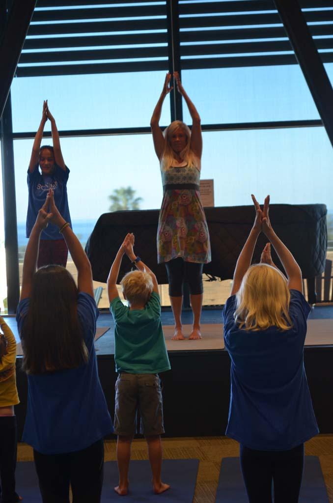 Shannon Rhondo, EUSD health and wellness instructor, leads young yogis in a yoga demonstration at the Wellness Week festival on Saturday. Photo by Tony Cagala