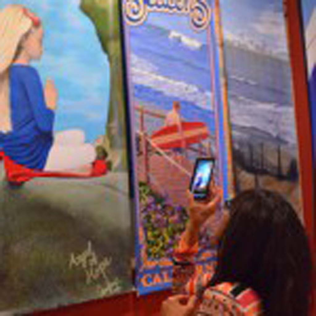 People wander through the former Cabo Grill restaurant in Cardiff on Saturday to view the unveiled art banners that will be hung from the street lampposts along Coast Highway 101. Photo by Tony Cagala