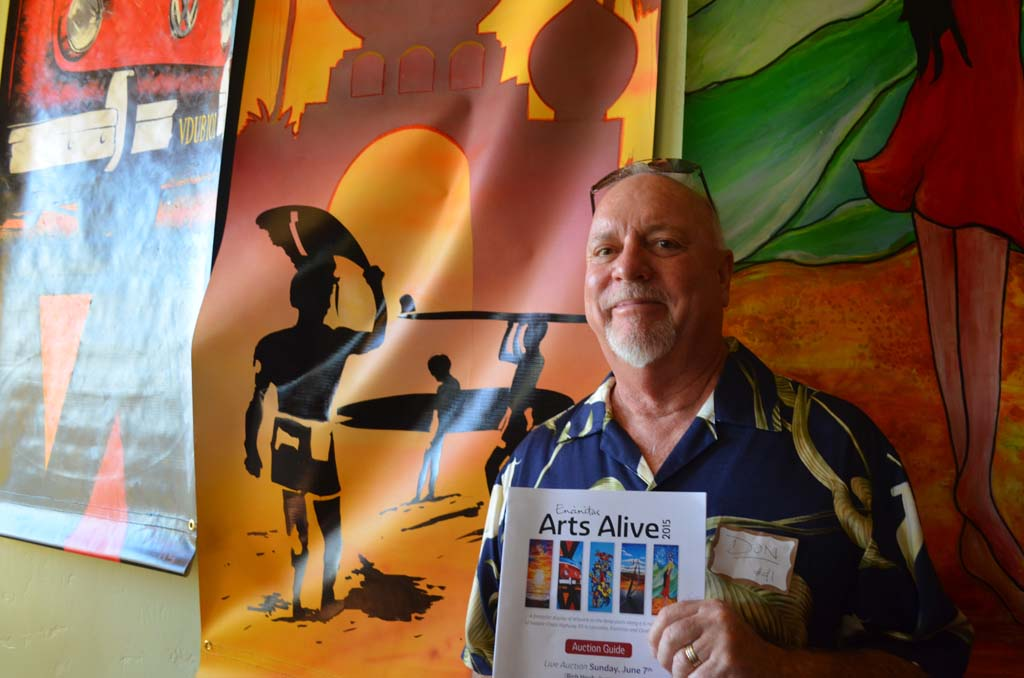 """Artist Don Doerfler stands next to his banner """"Endless Encinitas,"""" on Saturday. Photo by Tony Cagala"""