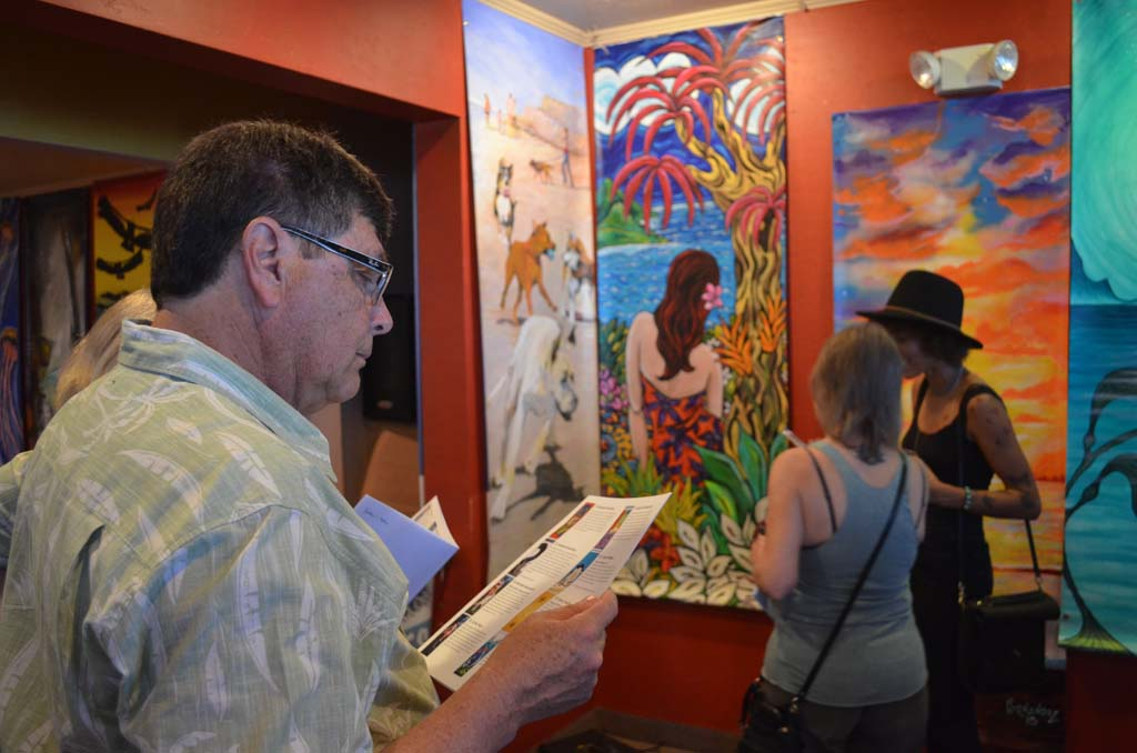 An art patron looks at the bidding program for the Arts Alive banners that were unveiled on Saturday. A live auction for the banners will be held June 7. Photo by Tony Cagala