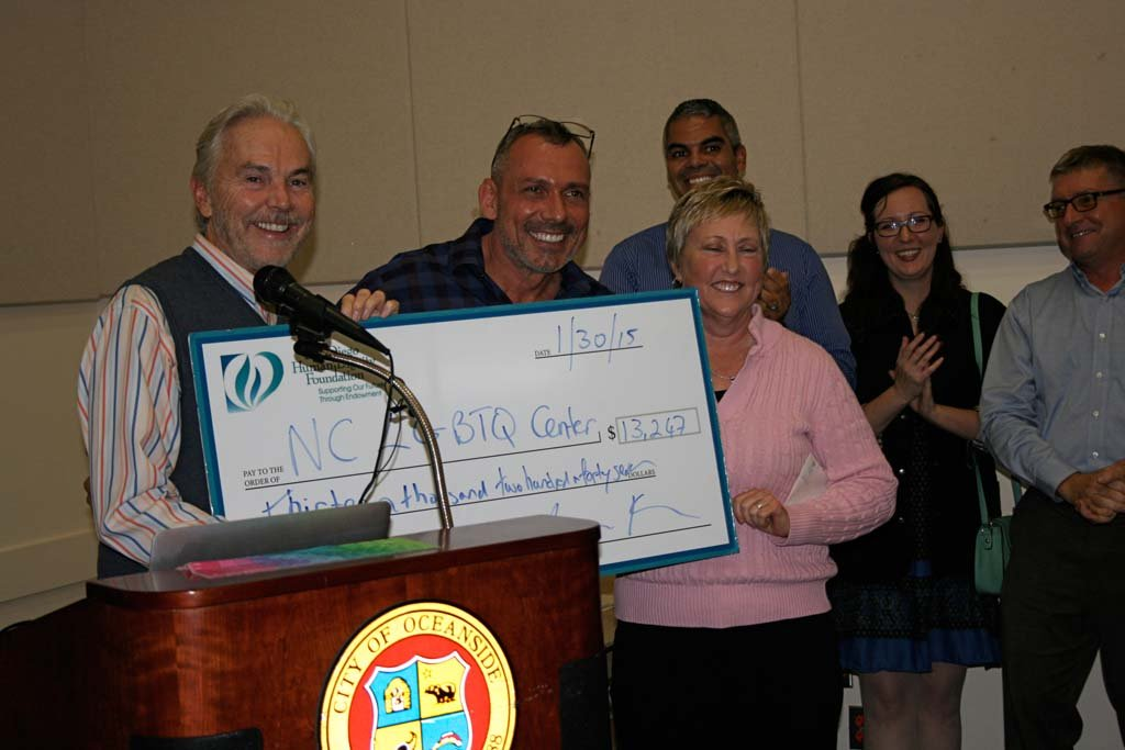 On far left San Diego Human Dignity Foundation executive director John Brown hands LGBTQ Center Executive Director Max Disposti a check to fund programs. The foundation gave the center the greatest amount in donations last year. Photo by Promise Yee