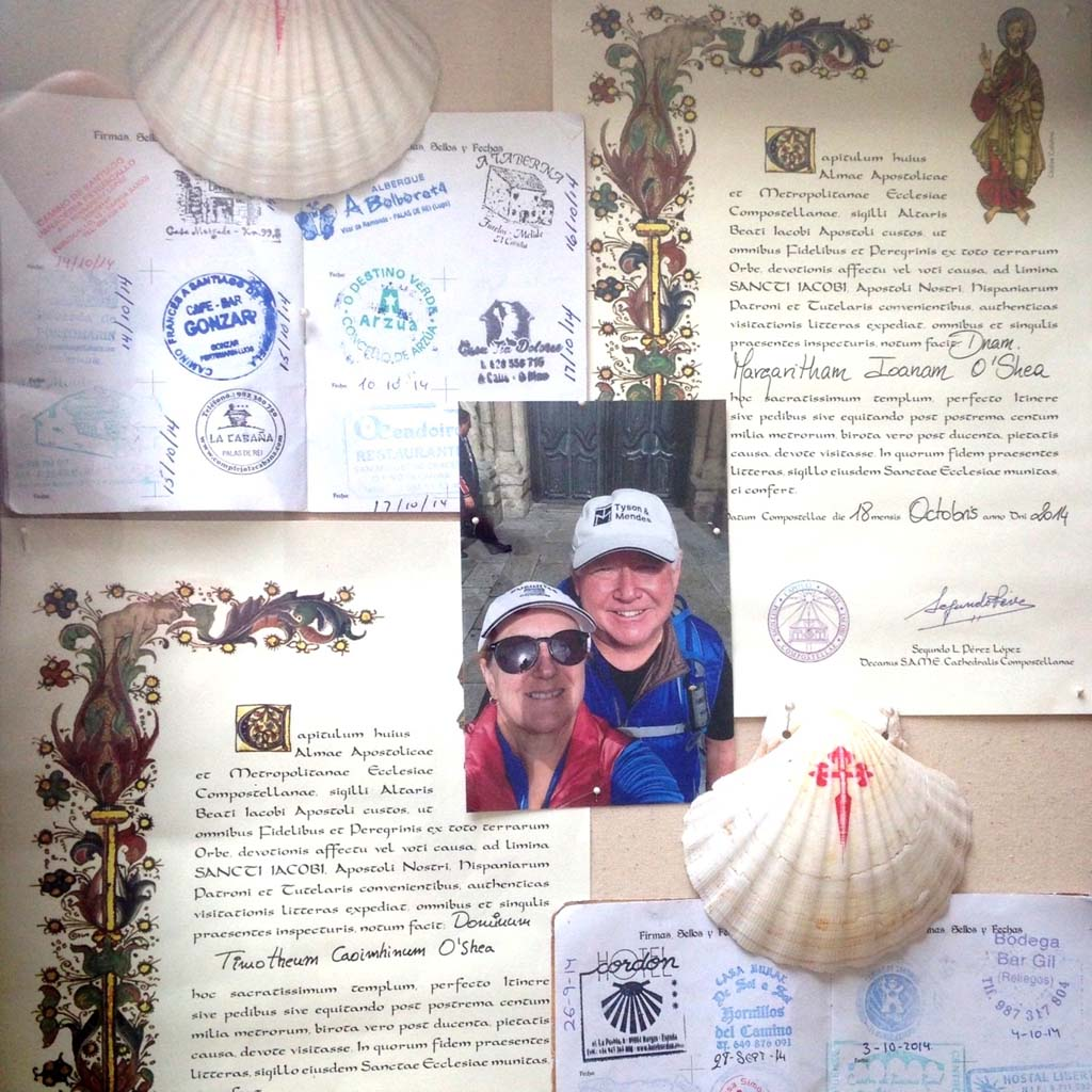 "Tim and Peggy O'Shea have framed the documents that verify their 500-mile, on-foot pilgrimage via the Camino de Santiago. Every inn, café and business along the way has a unique stamp which pilgrims collect in their ""credentials.""  Those who live along the Camino ""are very dedicated to it and their culture,"" Tim says. ""It shows; it's so clean."" When pilgrims reach trail's end at the city of Santiago and the Cathedral Santiago de Compostela, credentials are verified and pilgrims receive a certificate written in Latin that confirms they've completed the journey"