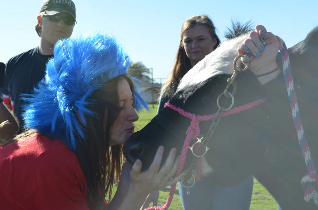 Bobier Elementary School Principal Shannon Garcia kisses Houston, a 1,000-pound Angus shorthorn cross steer, on Friday as part of a reward for students completing their Read Across America challenge. Photo by Tony Cagala