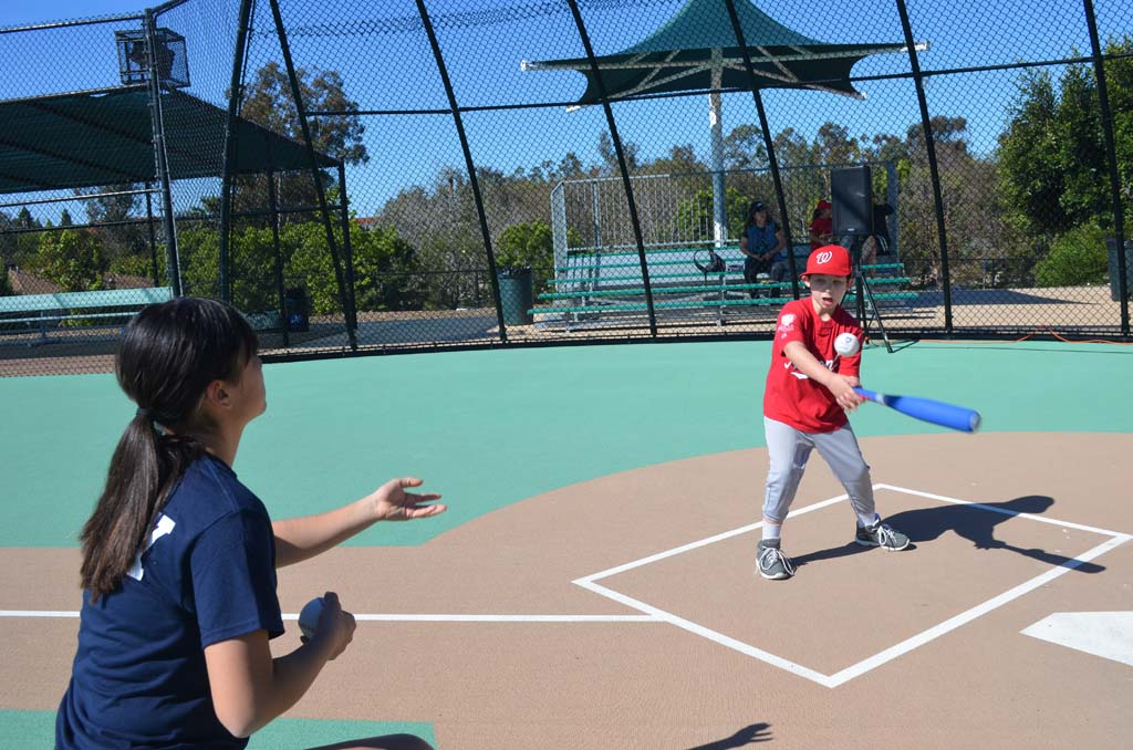 Miracle League volunteer Erin Coogan pitches to her buddy Douglas McPhail before Opening Day Ceremonies on Saturday. Photo by Tony Cagala