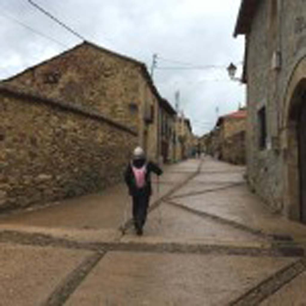 """Peggy O'Shea of San Marcos makes her way up a pebbled street in Rabanal del Camino, a village about two-thirds of the way to Santiago, the end of the 500-mile pilgrimage. """"We left there at 5:30 a.m.,"""" Tim O'Shea remembers. """"It was a long day because of the terrain. Rabanal is very old and very pretty, but very rustic."""""""