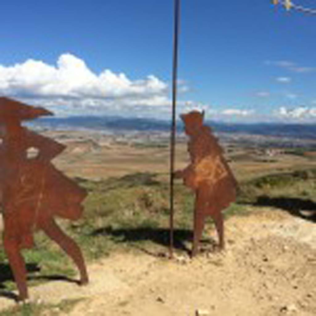 """Camino pilgrims leaving Pamplona soon arrive at the Alto de Perdon (Mountain of Forgiveness) at about 2,600 feet, where they encounter these large, metal-silhouette sculptures representing pilgrims on foot and horseback. It's a place where old meets new, Tim O'Shea explains. """"You have the sculptures representing pilgrims who have traveled the Camino for a thousand years, and high-tech wind turbines that supply energy to Pamplona."""""""