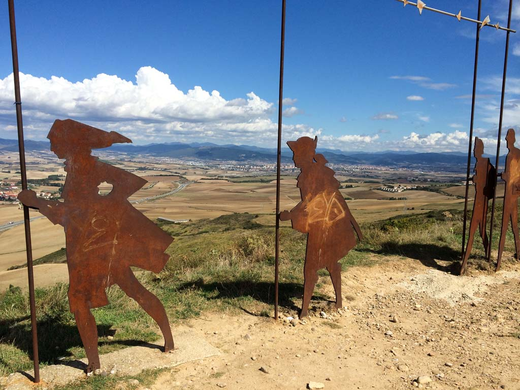 "Camino pilgrims leaving Pamplona soon arrive at the Alto de Perdon (Mountain of Forgiveness) at about 2,600 feet, where they encounter these large, metal-silhouette sculptures representing pilgrims on foot and horseback. It's a place where old meets new, Tim O'Shea explains.  ""You have the sculptures representing pilgrims who have traveled the Camino for a thousand years, and high-tech wind turbines that supply energy to Pamplona."""