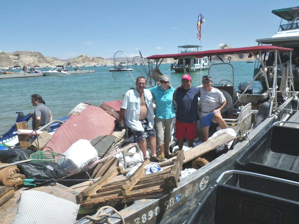 Volunteer Trash Trackers at Lake Powell bring in their weekly haul of garbage to a barge for removal. The refuse is picked up by the U.S. National Park Service.