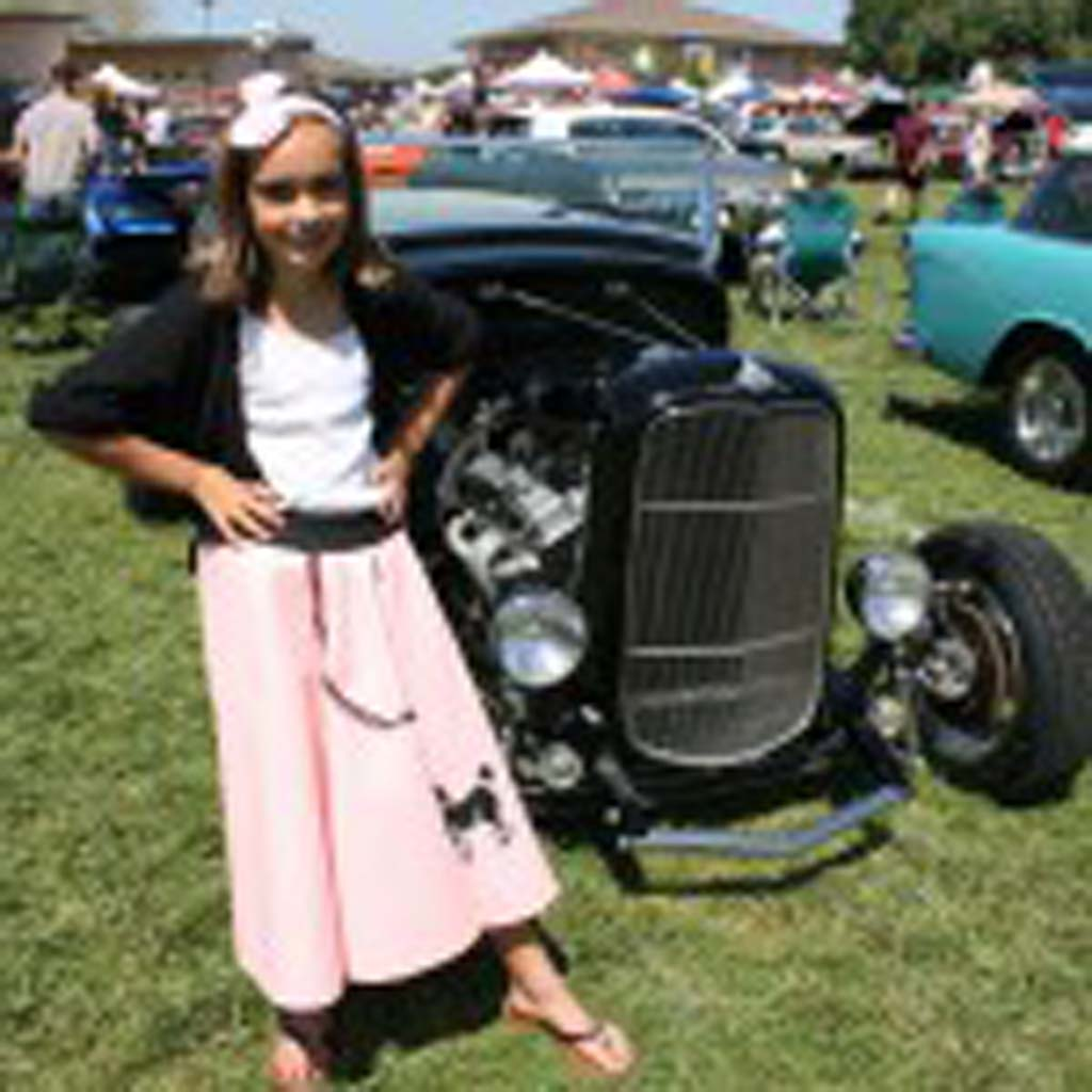 Katie Whaling, 10, of Oceanside, goes 50s-style for the car show. A custom hot rod is parked behind her. Photo by Promise Yee