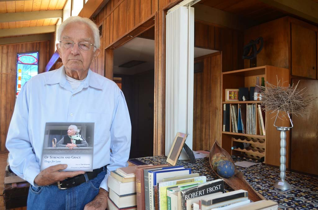 "Poet Tom Whayne, 90, with his first book of poems ""Of Strength and Grace: Elegy for Love"" at his Cardiff home. Whayne will be reading selections from his book at Ducky Waddles at 7 p.m. April 15. Photo by Tony Cagala"