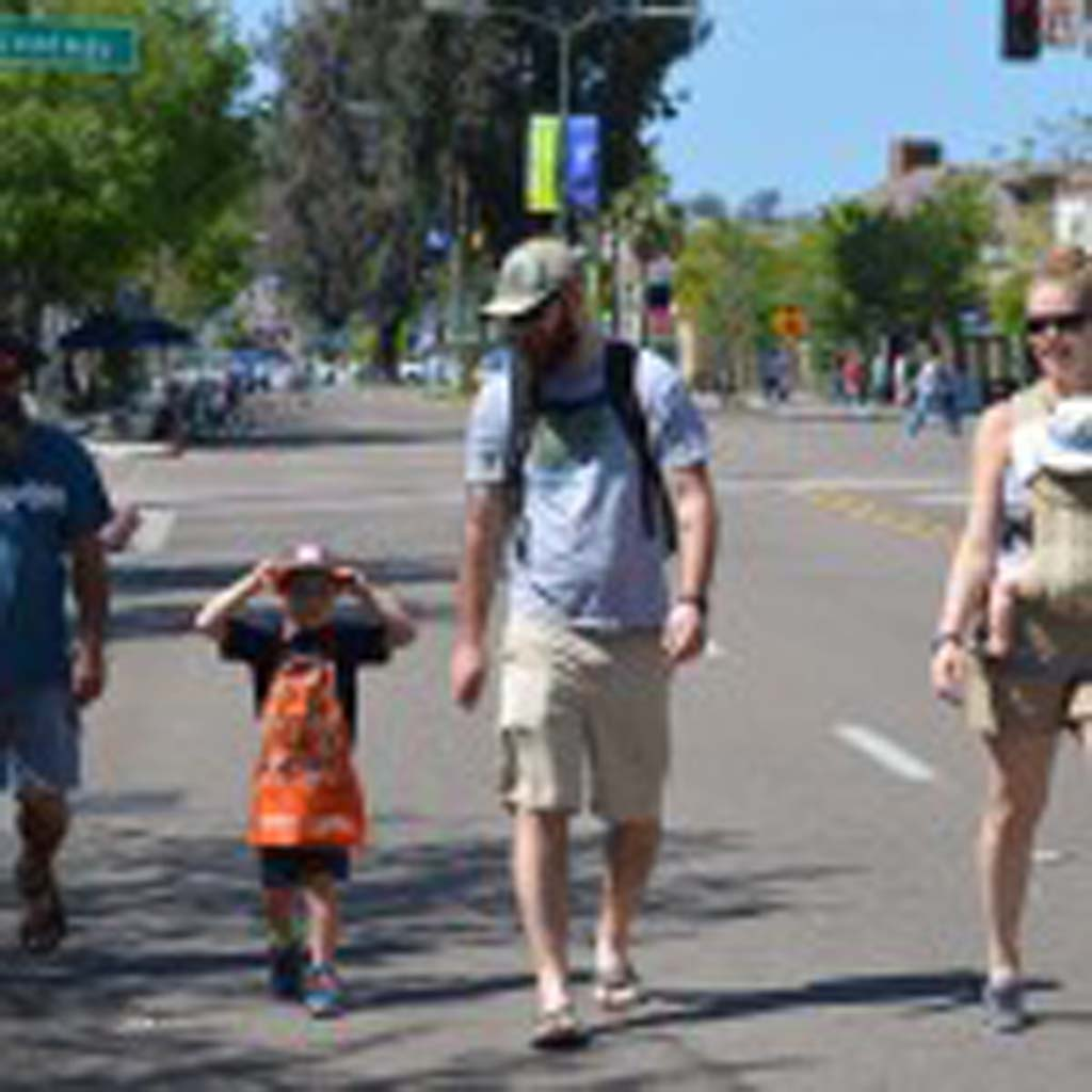 """From left: Scott Yoder, Joshua Hall, Robert Hall, Ahna Hall with 8-month-old Kieran Hall walk down Grand Avenue. """"It's not everyday you get to walk down the streets like this,"""" Ahna said. Photo by Tony Cagala"""