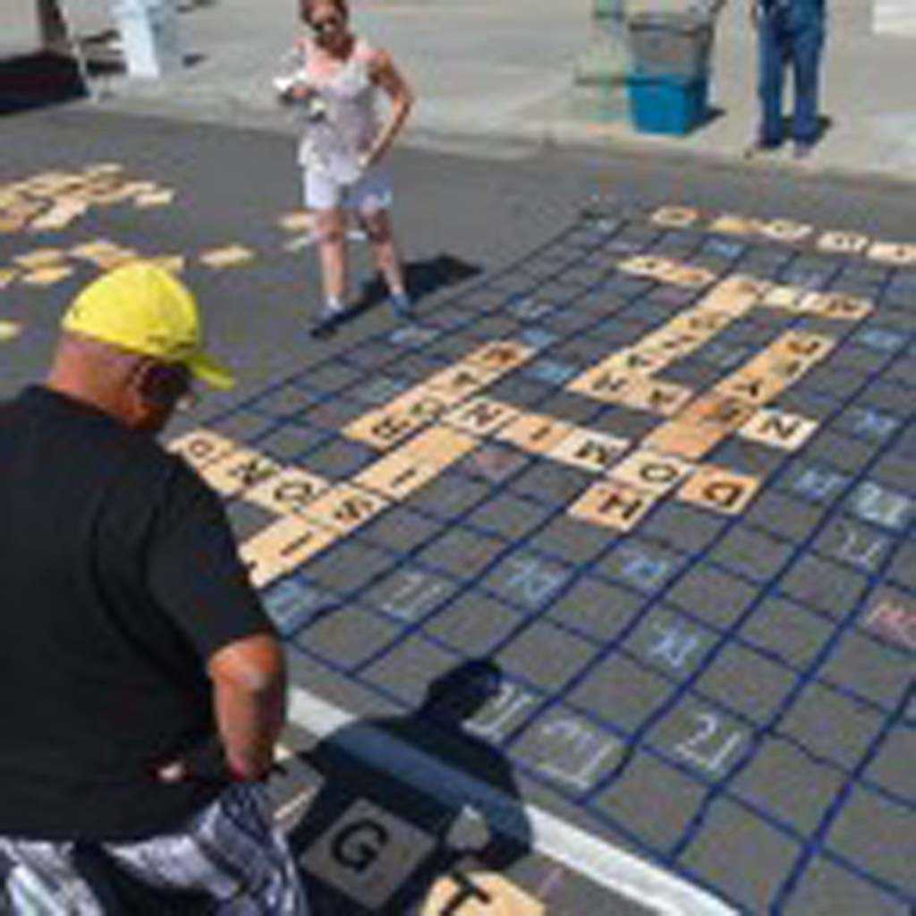 David Ramirez ponders his next word for a giant game of street Scrabble. Photo by Tony Cagala