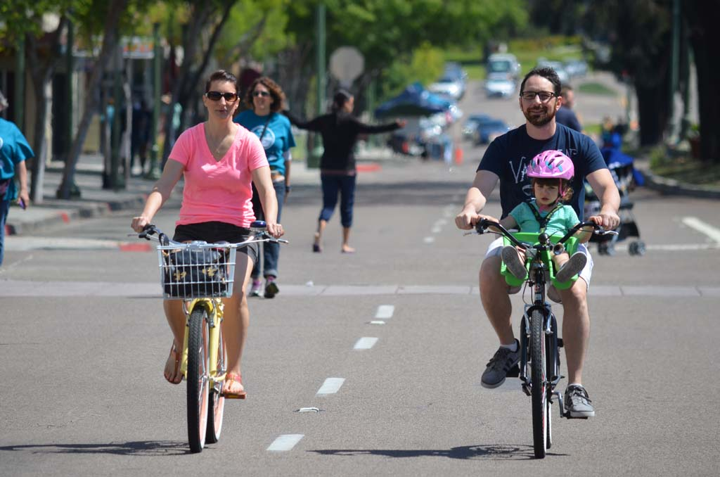 Traci Crogh, left, with Mike Crogh and Macy Crogh pedal down Escondido's Grand Avenue. Photo by Tony Cagala