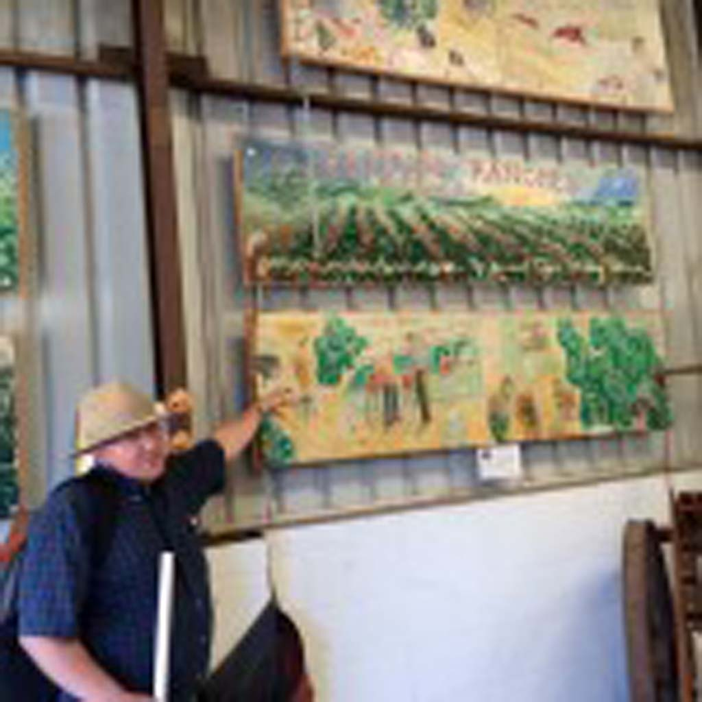 "George Thacher, great-grandson of the ranch's original owner, shows visitors paintings that depict the history of the Ojai Valley Ranch. The paintings hang in the packing house, which is open to visitors. Besides selling to locals and shipping to countrywide destinations, the family ships many pounds of Pixies to Japan annually. ""They've been eating them for years,"" says George's sister, Emily Ayala."