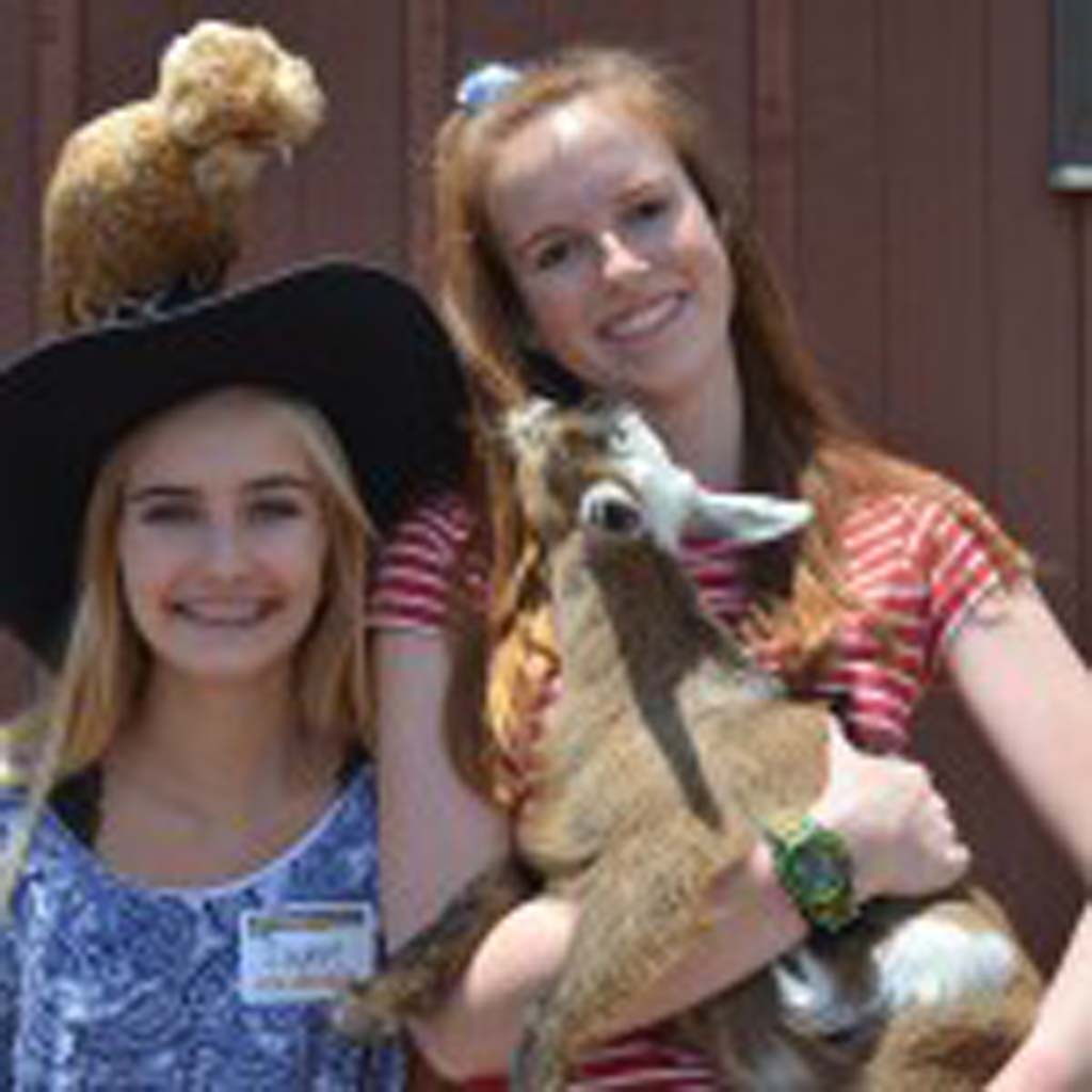 Sophie Bustamante, left, sports a Polish hen atop her head, while friend Colleen Coveney holds a pygmy goat from Cindy Lou's Petting Zoo. Photo by Tony Cagala