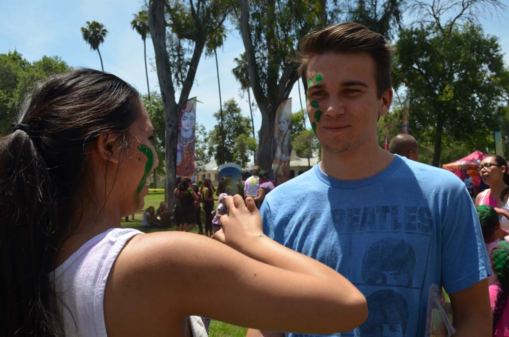 Allyson Pacifico, left, adds some colorful designs to Keanan Taylor-Jensen's face. Photo by Tony Cagala