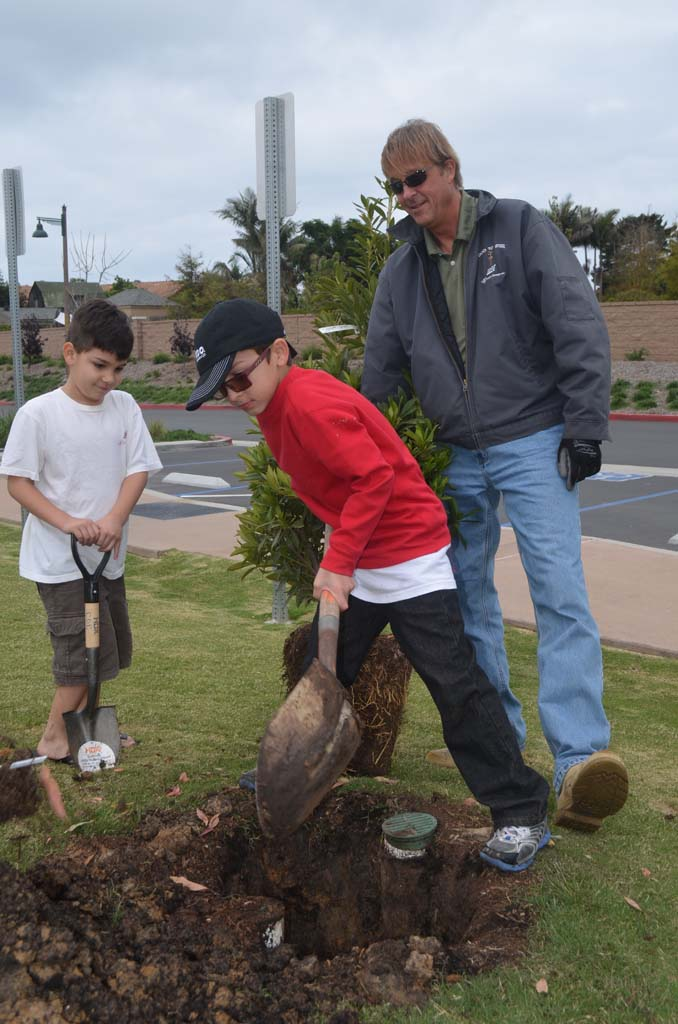 Brothers Benjamin Feura, left, and Sebastian Feura help dig out a spot for a new tree with the help of Greg Peck from SDG&E. Photo by Tony Cagala