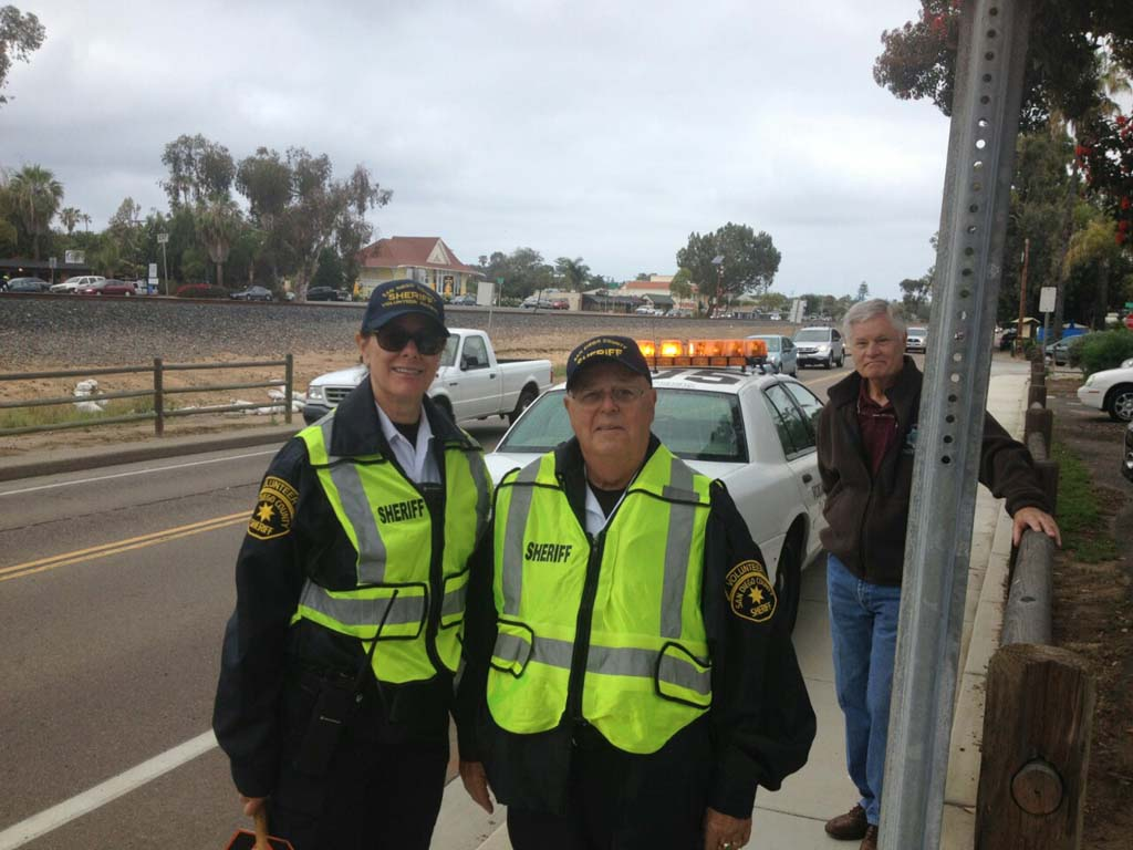 Encinitas Sheriff's volunteers Leslie Echter, left, Jerry Jerome, center, and Larry Peetoom, keep an eye out in front of Paul Ecke Central in an effort to slow down traffic that had been endangering students and their parents at the elementary school for some time. Photo by Aaron Burgin